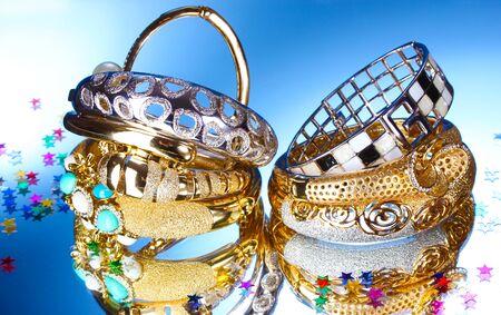 Beautiful gold bracelets on blue background Stock Photo - 13264952