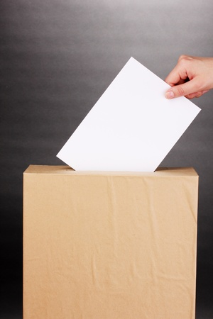 balloting: Hand with voting ballot and box on grey background