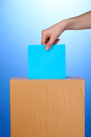 Hand with voting ballot and box on blue background Stock Photo - 13265460