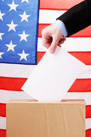Hand with voting ballot and box on Flag of USA Stock Photo - 13265552