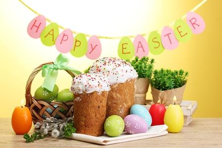 Красивые пасхальные куличи, красочные яйца в корзину и свечи на деревянный стол на желтом фоне Фото со стока - 13265478
