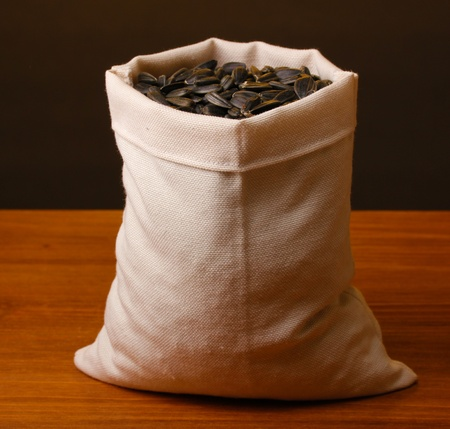 Cloth bag of sunflower seeds on wooden table on brown background photo