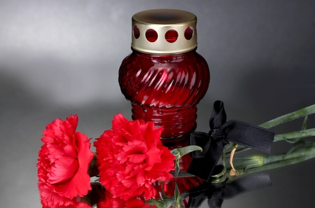 Memory lantern with candle,  carnations and black ribbon on grey background Stock Photo - 13267299