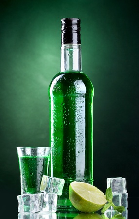 intoxicate: bottle and glass of absinthe with lime and ice on green background Stock Photo