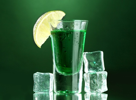 intoxicate: glass of absinthe, lime and ice on green background