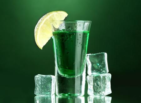 ajenjo: vaso de absenta, lima y hielo sobre fondo verde