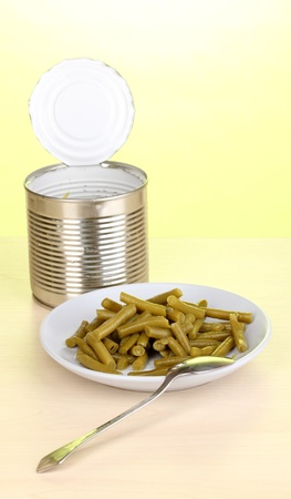 Open tin can and plate with french bean and spoon on wooden table on green background Stock Photo - 13267660