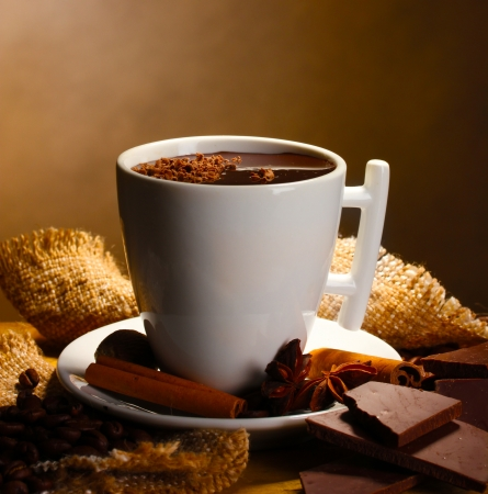hot drink: cup of hot chocolate, cinnamon sticks, nuts and chocolate on wooden table on brown background