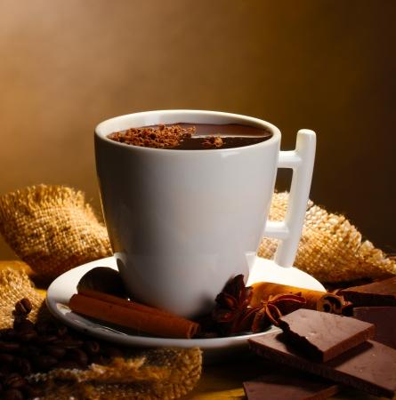 cacao: taza de chocolate caliente, los palitos de canela, nueces y chocolate en la mesa de madera sobre fondo marr�n Foto de archivo