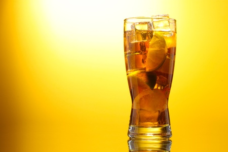 Iced tea with lemon and lime on yelow background photo