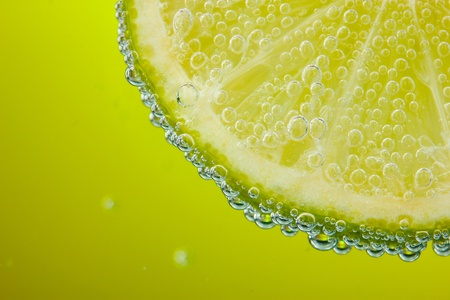 lime green: slice of lemon in the water with bubbles