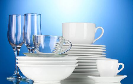 empty bowls, plates, cups and glasses on blue background Stock Photo - 13374269