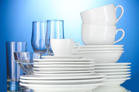 empty bowls, plates, cups and glasses on blue background photo