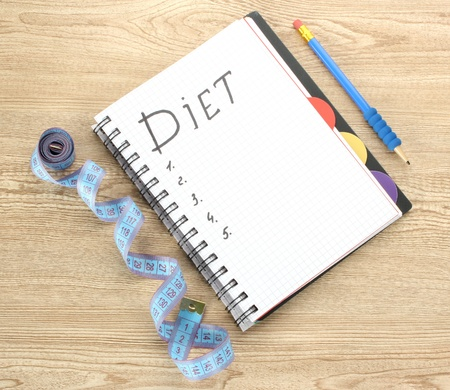 Planning of diet. Notebook measuring tape and pen on wooden table Stock Photo - 13374218