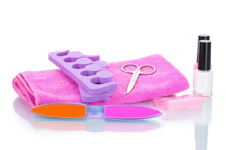 Pedicure set on pink towel isolated on white photo
