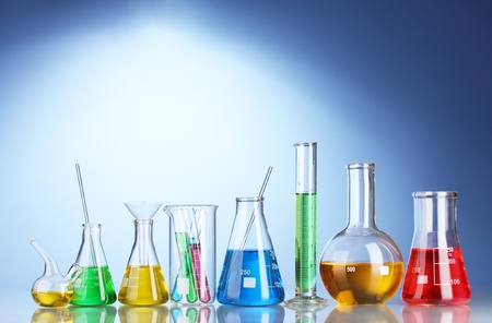 Different laboratory glassware with color liquid and with reflection on blue background photo
