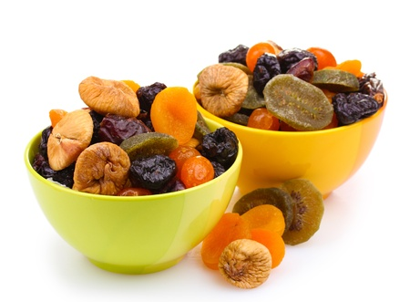 Dried fruits in bright bowls isolated on white photo