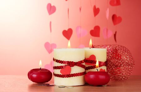 candles for Valentine's Day on wooden table on red background Stock Photo - 13374149