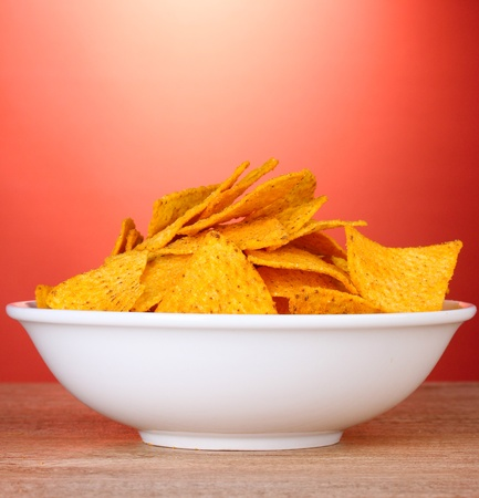 tasty potato chips in white  bowl on wooden table on red background photo