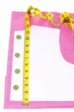 Measuring tape, buttons and pattern on fabric isolated on white photo