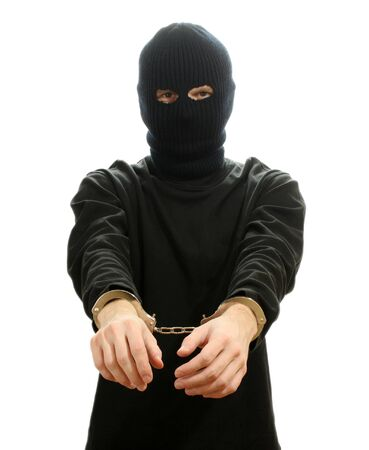 Bandit in black mask handcuffed isolated on white photo