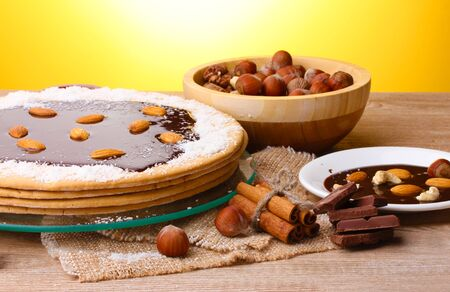 cake on glass stand and nuts on wooden  table on yellow background photo