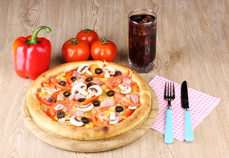 Aromatic pizza and cola on wooden background photo