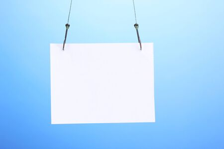 Empty sheet of a paper on fish hooks on blue background photo