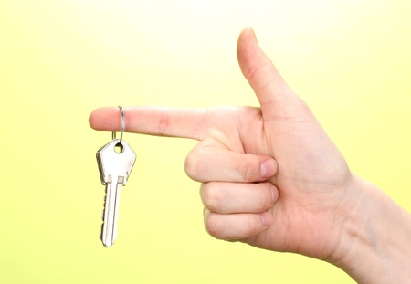 Keys in hand on green background photo