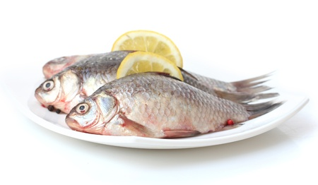 Fresh fishes with lemon on plate isolated on white Stock Photo - 13374644