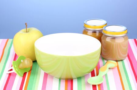 Jars of baby puree with plate and spoon on napkin on blue background Stock Photo - 13374129