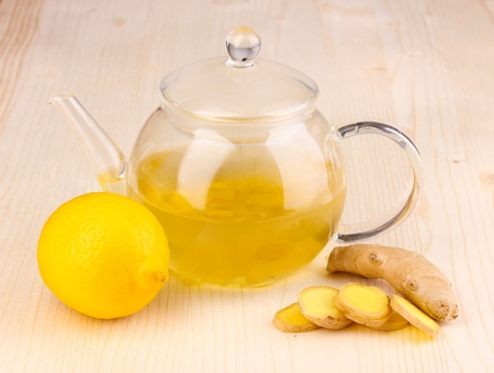Healthy ginger tea in kettle with lemon on wooden background photo