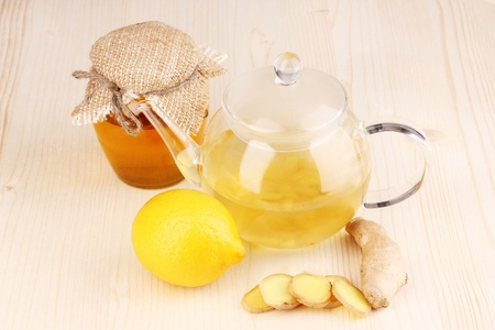 Healthy ginger tea in kettle with lemon and honey on wooden background photo
