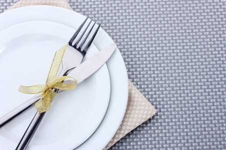 white napkin: White empty plates with fork and knife tied with a ribbon on a grey tablecloth Stock Photo
