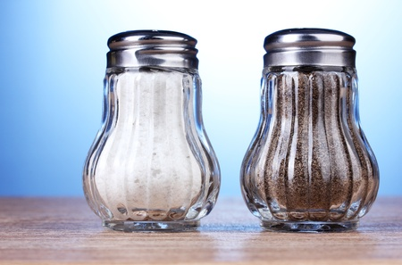Salt and pepper mills on wooden table on blue background photo