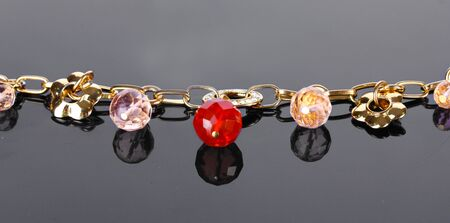 Beautiful golden bracelet with precious stones on grey background Stock Photo - 13374230