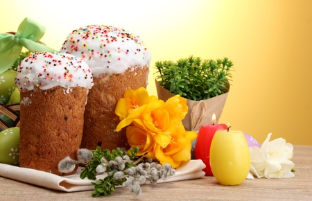 Beautiful Easter cakes, colorful eggs and candles on wooden table on yellow background photo