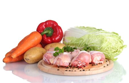 Fresh vegetables with raw chicken drumsticks and pork steak on cutting board isolated on white photo