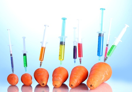 Injection into fresh carrot on blue background photo