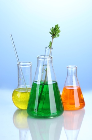 Different laboratory glassware with color liquid on blue background photo