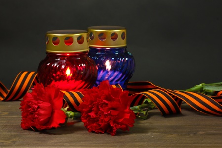 Memory lantern with candles, red carnations and St. George ribbon on wooden table on grey background photo