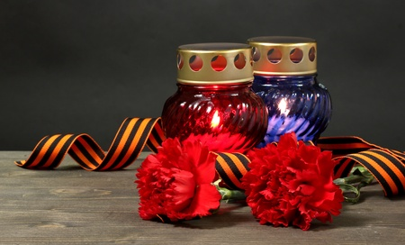 Memory lantern with candles, red carnations and St. George ribbon on wooden table on grey background Stock Photo - 13373867