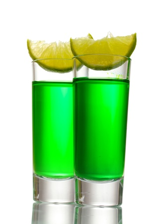 intoxicate: glasses of absinthe and lime isolated on white