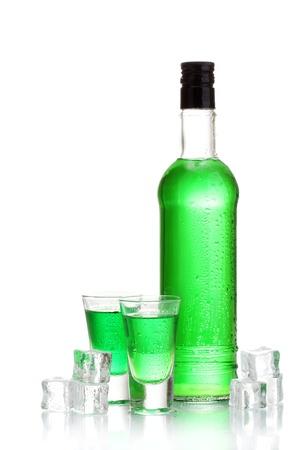 ajenjo: botella y los vasos de absenta con hielo aislados en blanco