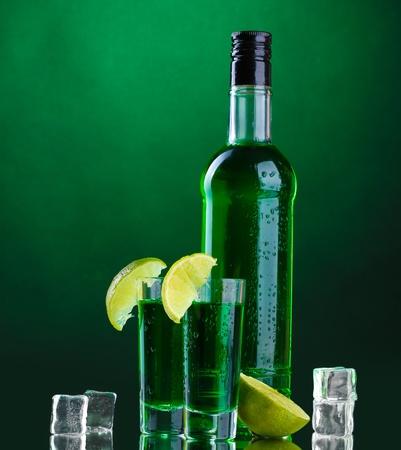 Bouteille et des verres d'absinthe avec de la chaux et de la glace sur fond vert Banque d'images - 13374281