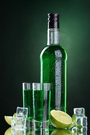 Bouteille et des verres d'absinthe avec de la chaux et de la glace sur fond vert Banque d'images - 13373805