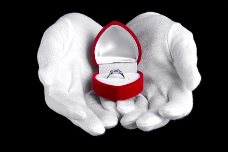 Man's hands holding ring in box on black background photo