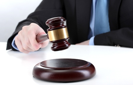 judge hammer: wooden gavel in hand on gray background Stock Photo