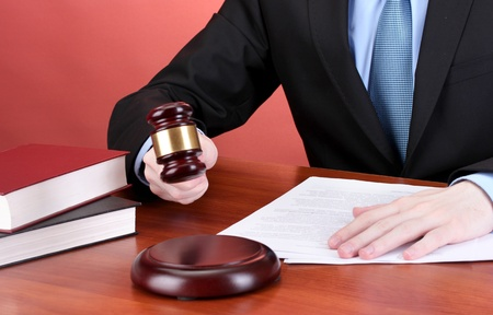 court judge: wooden gavel in hand and books on wooden table on red background