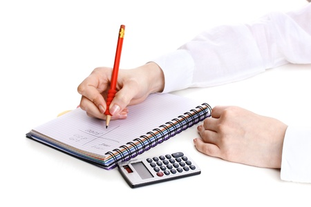 women hands with pencil, notebook and Calculator isolated on white photo